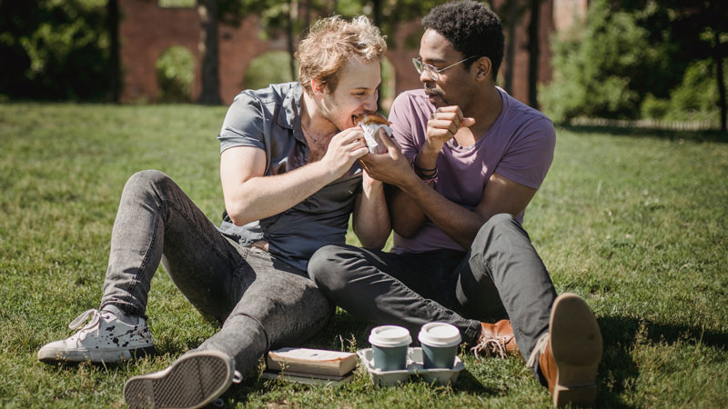 An outdoor image of a couple on a picnic, with one partner biting down on a sandwich as they laugh together