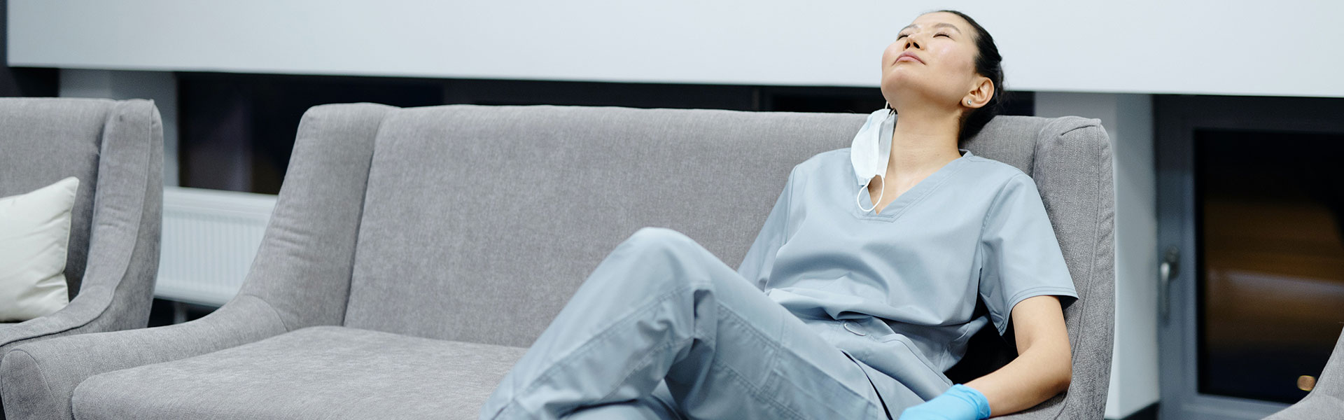 An image of a health care worker resting on a couch