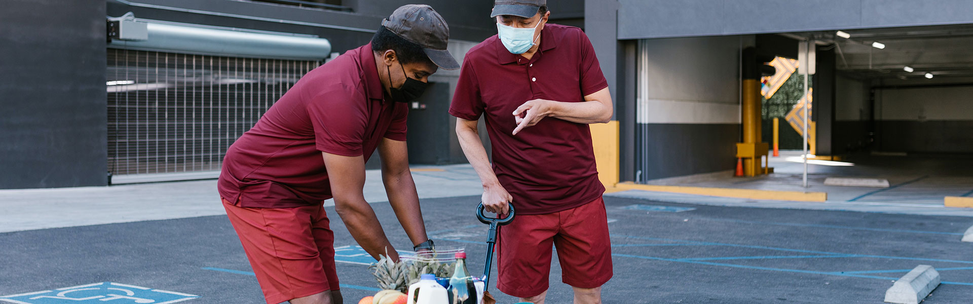 An outdoor image of wo workers wearing masks while delivering groceries