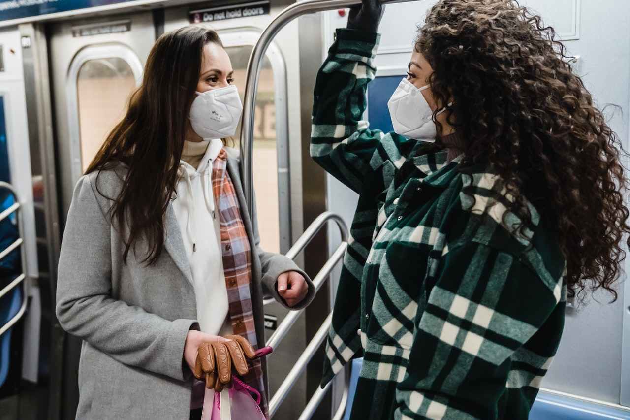 An image of two women wearing masks and interacting while taking public transit